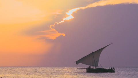 A beautiful sunset shot of dhow sail boat sailing off the coast of Zanzibar Footage