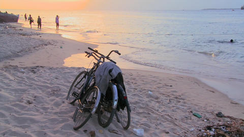 Sunset shot along a beach with two bicycles parked on the shore and children playing in distance Footage