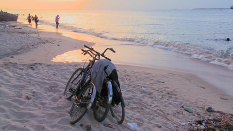 Sunset shot along a beach with two bicycles parked on the... Stock Video Footage