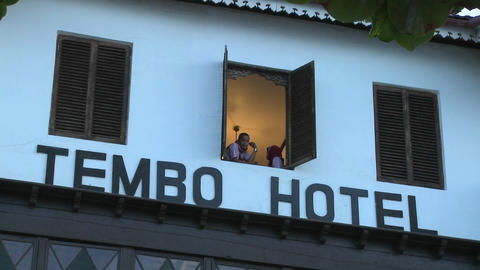 Two girls look out of a tropical beach hotel window Footage