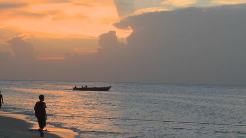 A small motorboat heads out at sunset as people walk on... Stock Video Footage