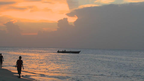 A small motorboat heads out at sunset as people walk on the beach at Stone Town, Zanzibar Footage