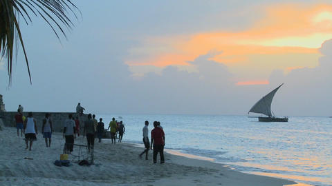 A dhow sailboat sails off the coast of Zanzibar at sunset Stock Video Footage