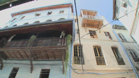 A low angle shot looking directly up at tall old buildings lining the narrow alleys of Stone Town, Z Footage