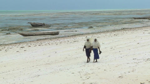Two Islamic girls walk in school outfits along a white sand beach Footage