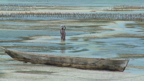 A woman walks through the tide with a load on her head in... Stock Video Footage