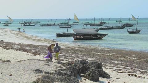 Two Muslim women walk along a beach in Zanzibar with dhow... Stock Video Footage