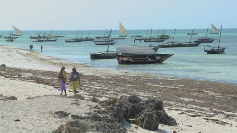 Two Muslim women walk along a beach in Zanzibar with dhow sailboats in the background Footage