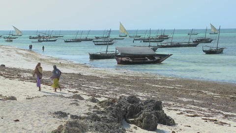 Two Muslim women walk along a beach in Zanzibar with dhow... Stock Video Footage