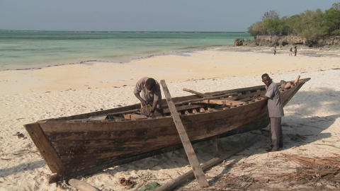 Two men work on building a boat on the coast of Zanzibar Stock Video Footage