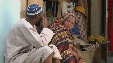 Two vendors sit and talk on the streets of Stone Town... Stock Video Footage
