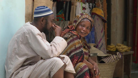 Two vendors sit and talk on the streets of Stone Town Zanzibar Footage