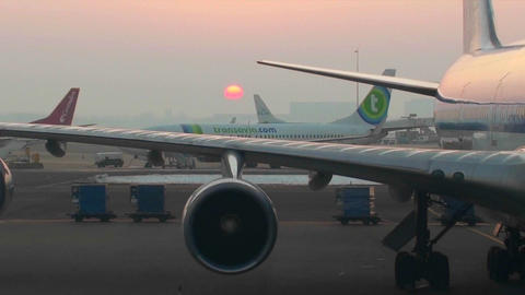 Traffic moves on a busy runway at sunset at an airport Stock Video Footage