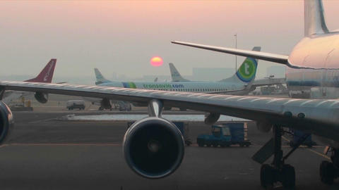 Traffic moves on a busy runway at sunset at an airport Footage