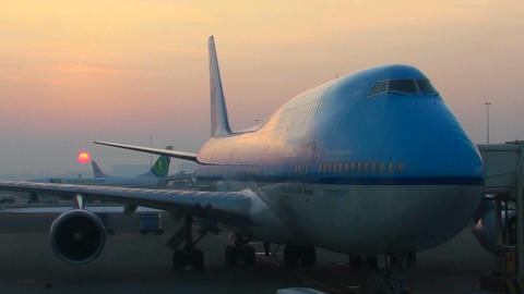 Sunrise behind a modern 747 at the boarding gate of an airport Footage