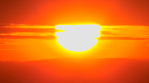 The sun slowly sets through the clouds in a huge orange ball Stock Video Footage