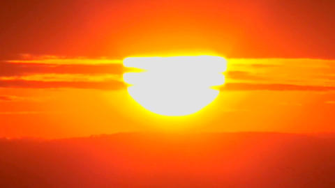 The sun slowly sets through the clouds in a huge orange ball Footage