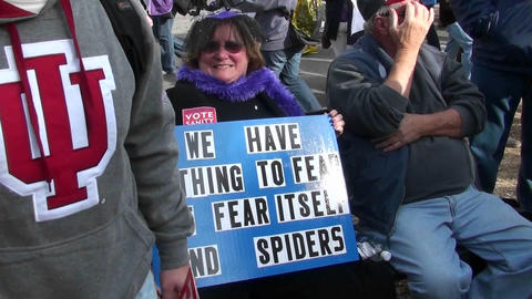 A woman holds a sign proclaiming her fear of spiders Stock Video Footage
