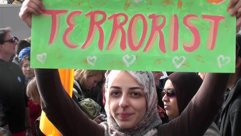 A Muslim woman holds up a sign imploring people not to call her a terrorist at the Jon Stewart rally Footage