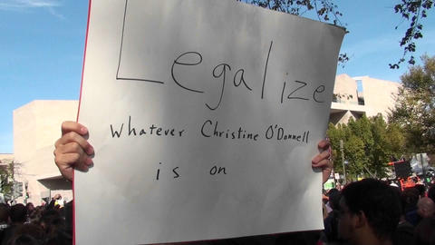 A man holds up a sign saying legalize whatever Christine O'Donnell is on at the Jon Stewart rally Footage