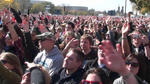 People wave their arms at a giant outdoor gathering Stock Video Footage