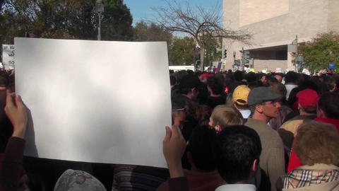 A blank sign is held up at a rally on which you can put... Stock Video Footage