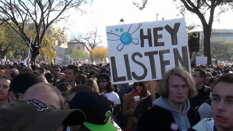 A sign at a huge political rally says Hey Listen Stock Video Footage