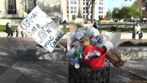 An Obama poster sits in a garbage can after a rally Stock Video Footage