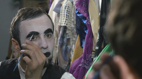 Handsome young man applying black paint on eyebrows for mime make-up Footage