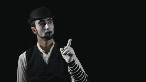 Young funny mime showing and pointing at something and approving Footage