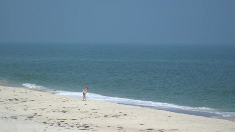 Bikini clad woman walking along Ho Hum beach on Fire Island Footage