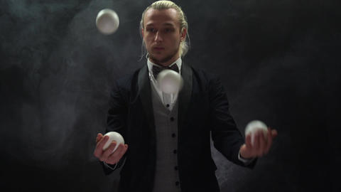 businessman wearing a suit juggling white balls. Success and management Live Action