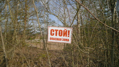 STOP RESTRICTED AREA sign in russian at fence on barbed wire outdoors in summer Live Action