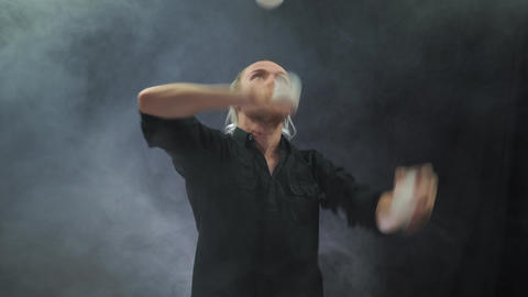 Man wearing a black juggling with white balls. Management, control and success Live Action