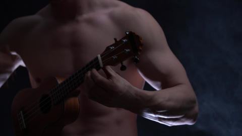 Young muscular male musician plays a ukulele ob black background with smoke Live Action