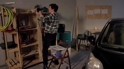 Guy parses things on the shelves of his garage Live Action