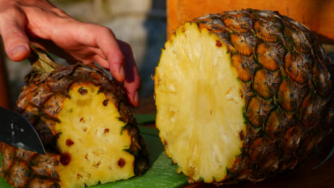 A man cuts a pineapple, close-up Live Action