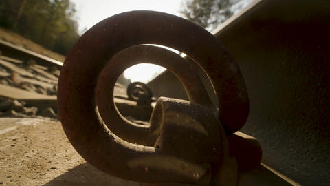 A macro shot of the rails of a railroad track through the fasteners on sunset Live Action