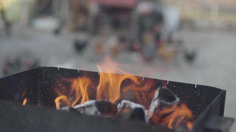 Close-up of red flame burning in barbeque grill as old blurred Caucasian woman Live Action
