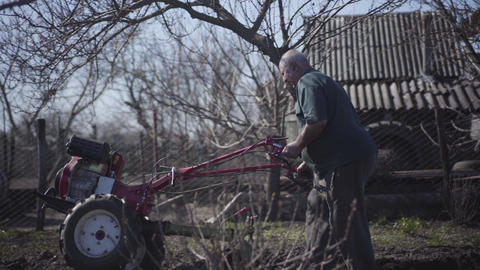 Side view of mature Caucasian male farmer making furrows with furrower. Elderly Live Action