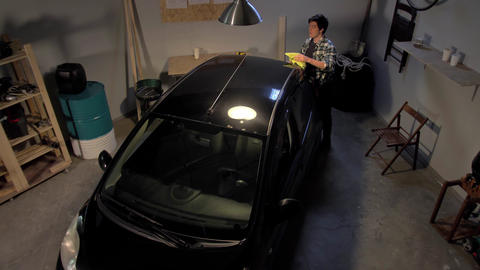 Guy washes a car in the garage Live Action