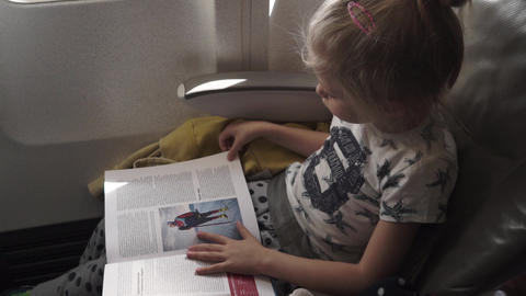 Stockholm - Sweden - 22-09-2019- Little child girl reads travel magazine flying on a plane trip Live Action