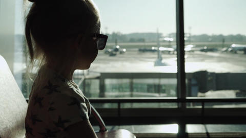 Child girl in sunglasses waiting for a plane at sunset sits at airport passenger terminal waiting Live Action