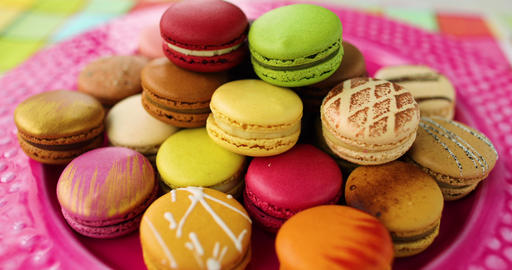 Many french macarons selection of colorful pastries on pink dessert plate. Retro Live Action