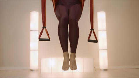 Sportswoman practicing yoga in hammock at studio. Girl exercising fly yoga Live Action