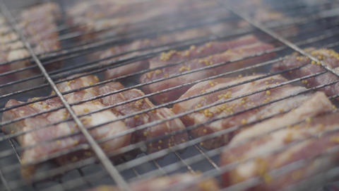 Close-up of medium rare pork ribs turning on barbecue grill. Baked meat in bbq Live Action