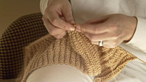 Womens hands are knitted with needles on a sunny day Live Action