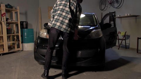 A man checks that under the hood of the car Live Action