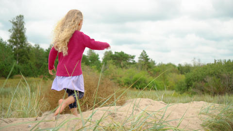 Five years old blonde girl with pink shirt walking barefoot on top of dune sand Live Action