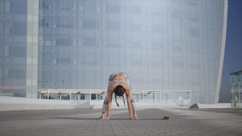 Woman performing yoga in urban street. Lady doing garland pose on mat outdoors Live Action